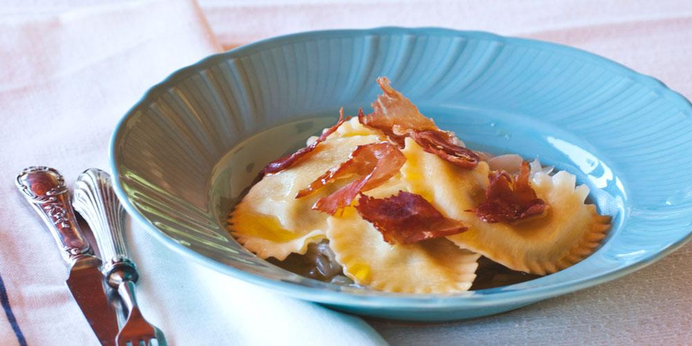 Granpanzerotti ricotta, spinaci e scorza di limone su letto di cipollata all'origano e petali di prosciutto croccanti